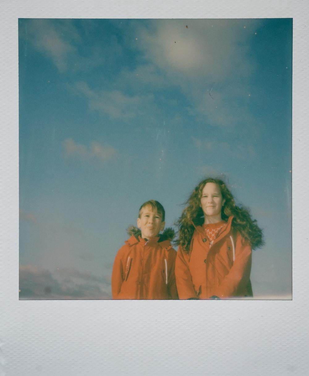 girl and boy wearing orange jackets standing