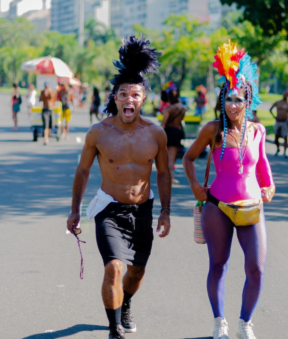 topless man walking beside woman during daytime