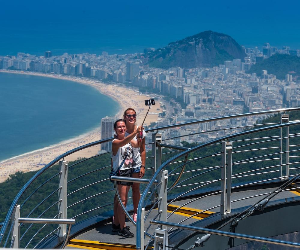 2 women taking photo atop of building during daytime