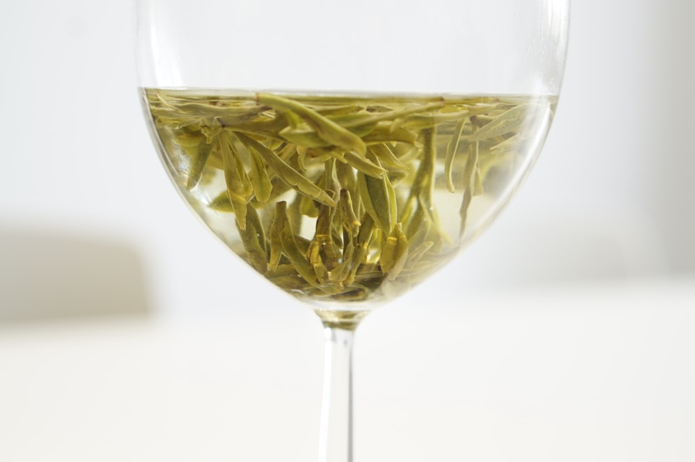 green flower petals in clear glass goblet