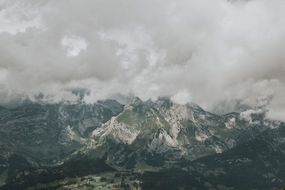 white clouds above green and grey mountains