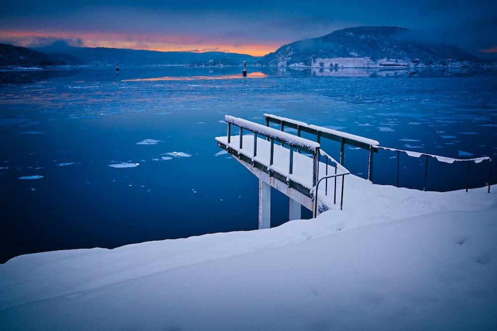 bridge covered by snow near calm water