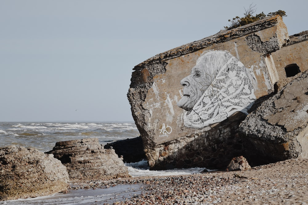 white woman with shawl drawing on concrete block in beach