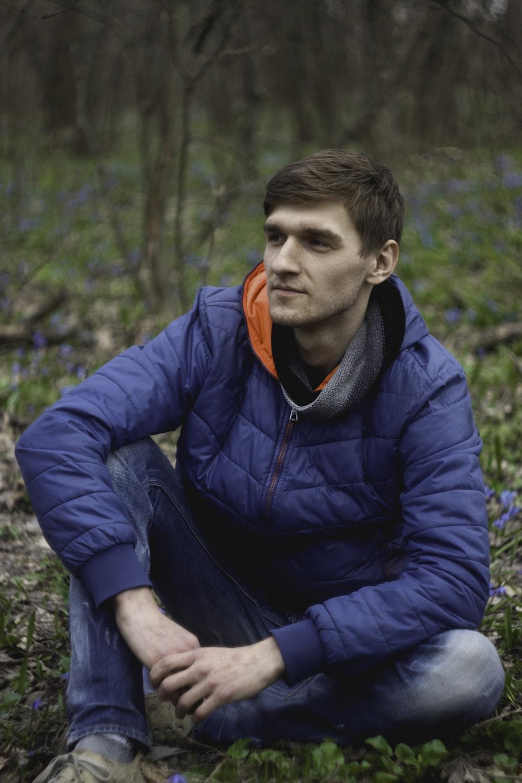 man sitting on green grass wearing blue bubble jacket