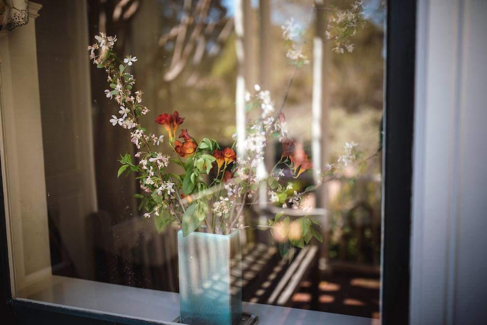 flowers in vase behind clear glass window