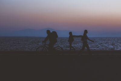 creative unfocused humans wallpaper pattern of fuzzy walking people silhouettes on dark twilight waterfront along Pacific ocean and unfocused mountain horizon background in evening sunset time
