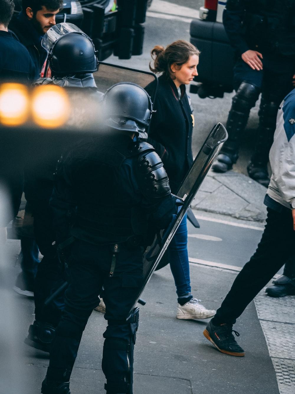 woman walking in front of two men carrying shields