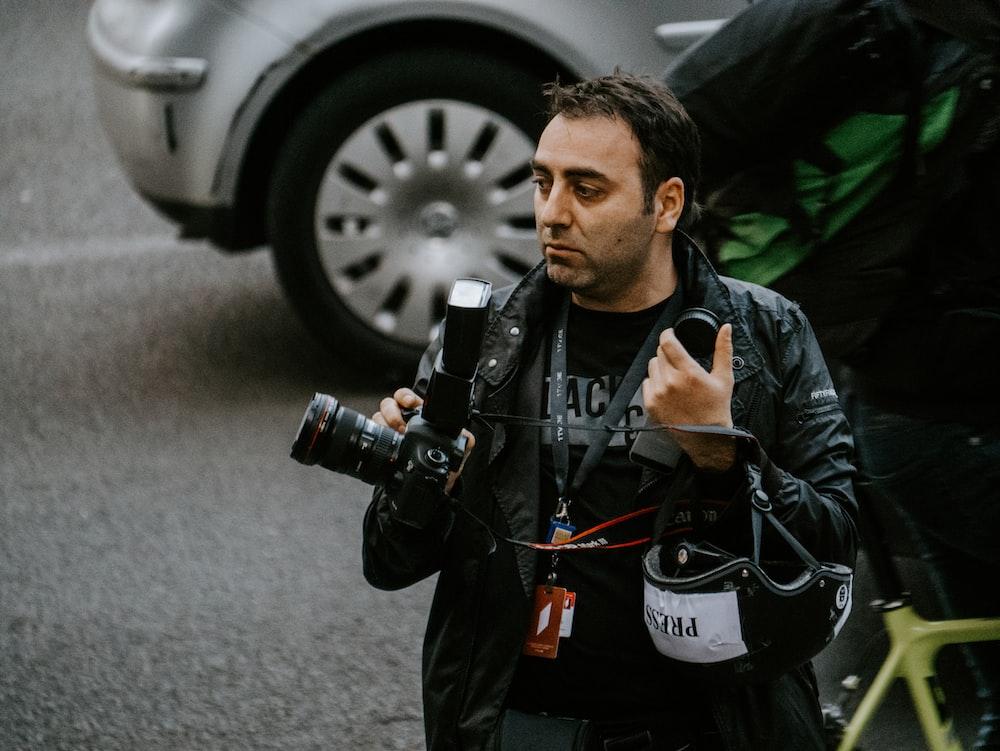man holding camera standing near SUV
