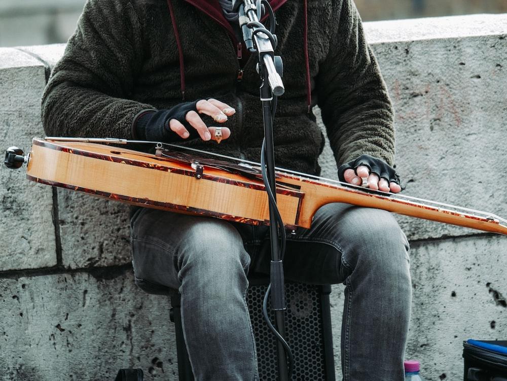 person playing guitar white singing