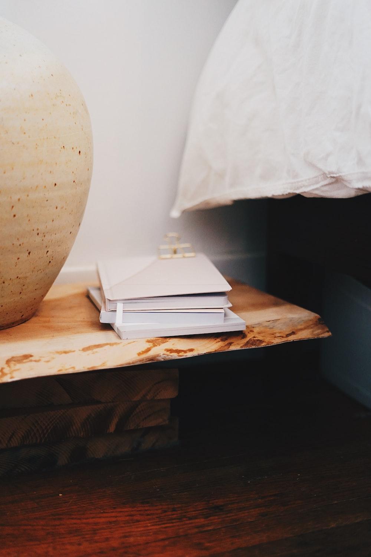 pile of books near ceramic vase