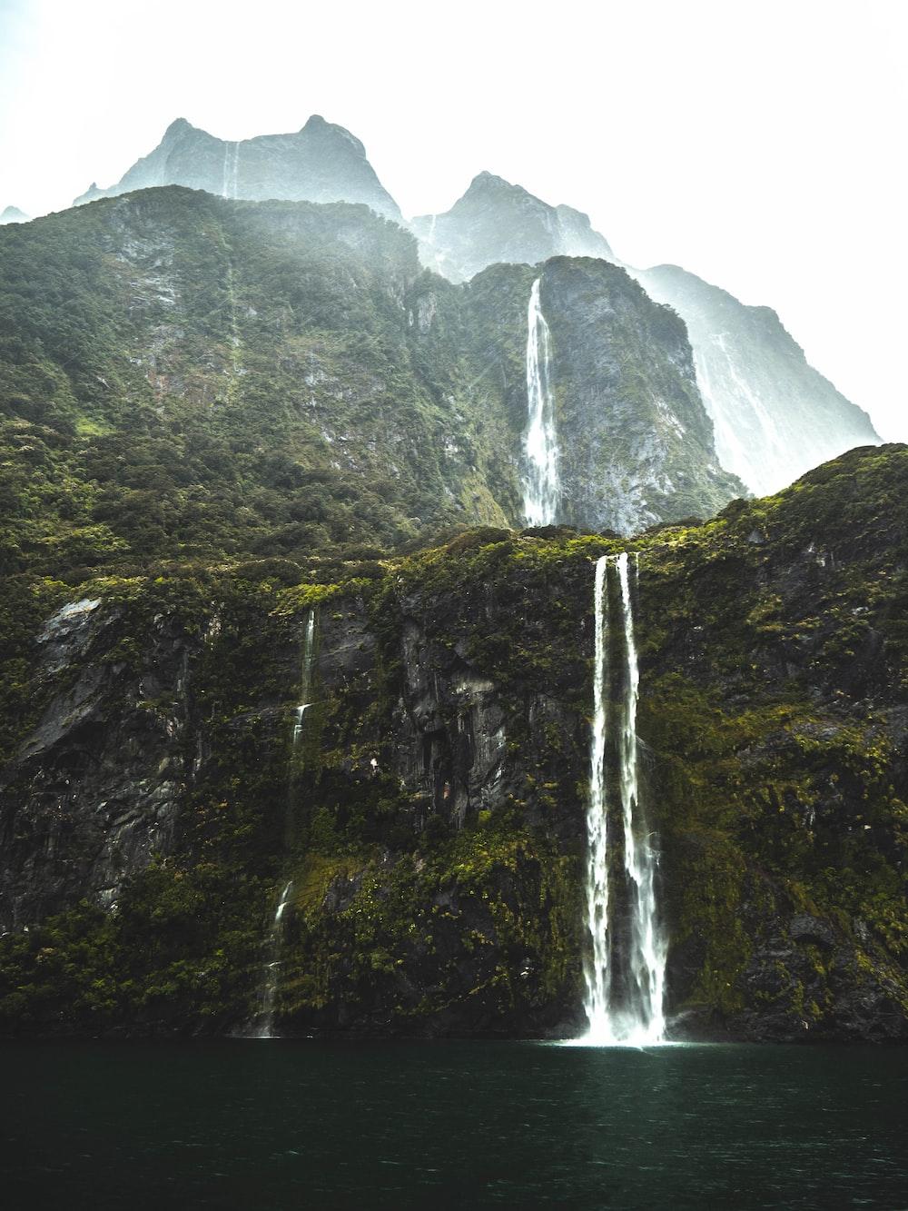 waterfalls under white sky