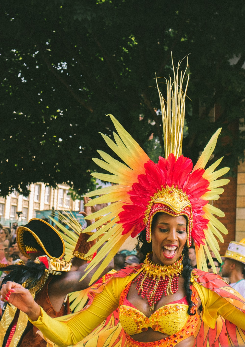 woman wearing yellow and red costume dancing in the middle of event