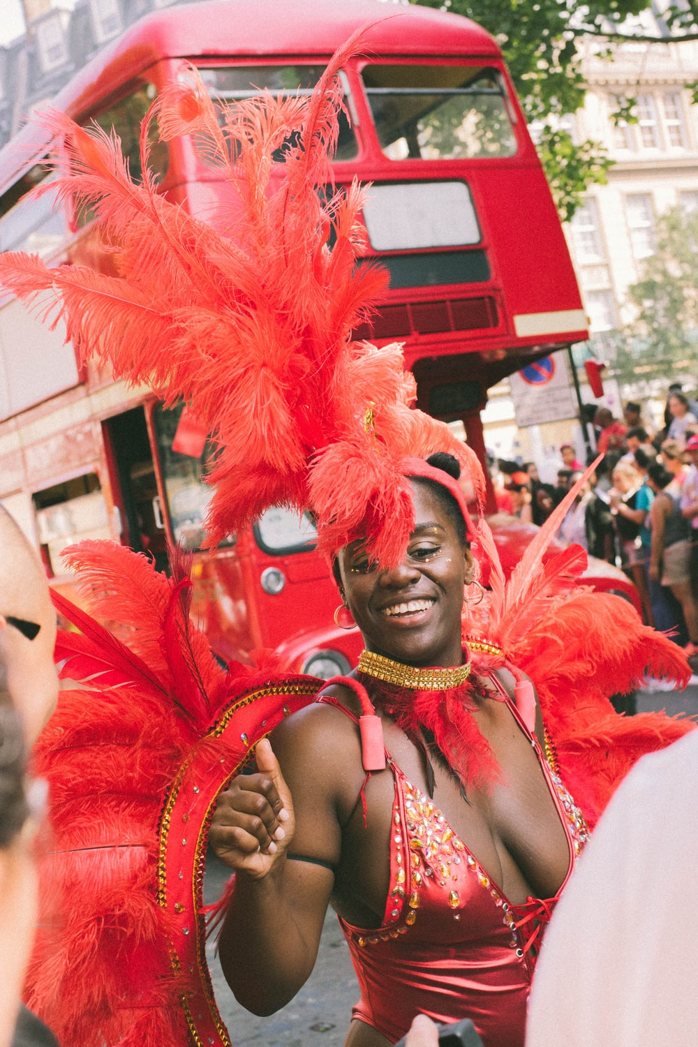 woman wearing red costume dancing near red bus