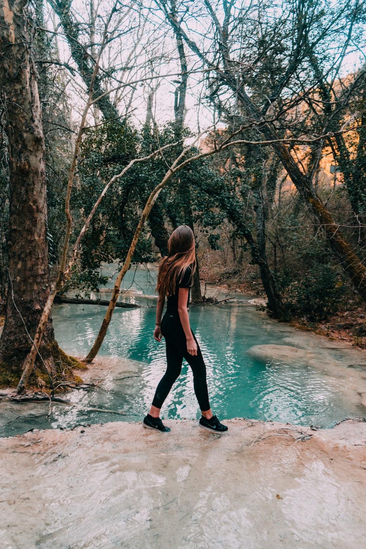 woman wearing black shirt walking on lake
