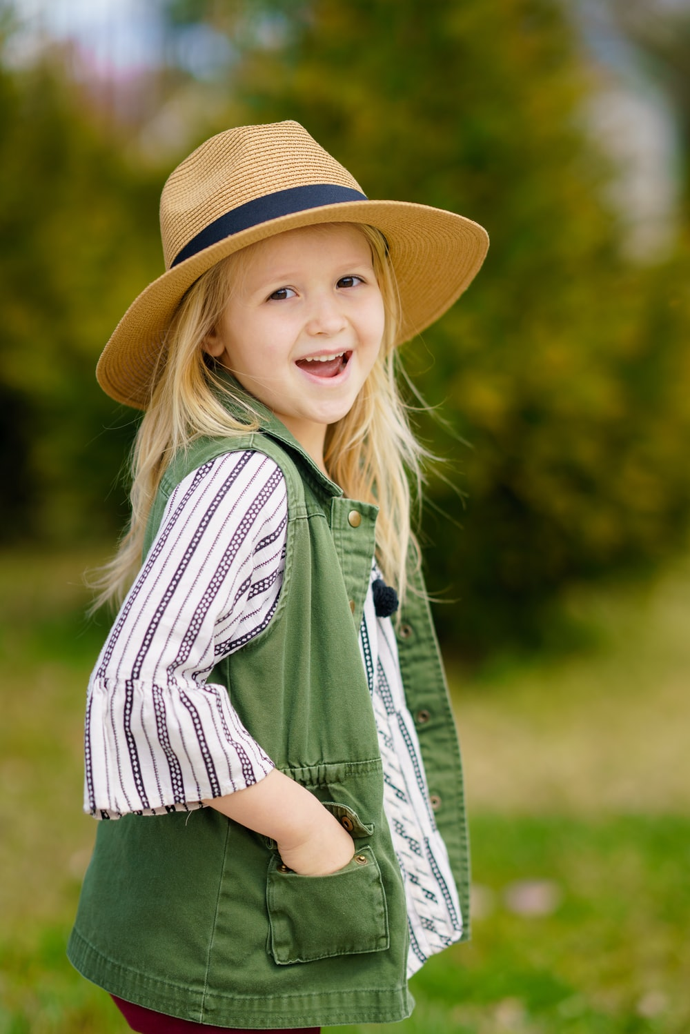 selective focus photography of girl smiling wearing sun hat