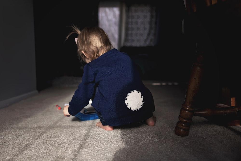 girl wearing blue jacket sitting on floor