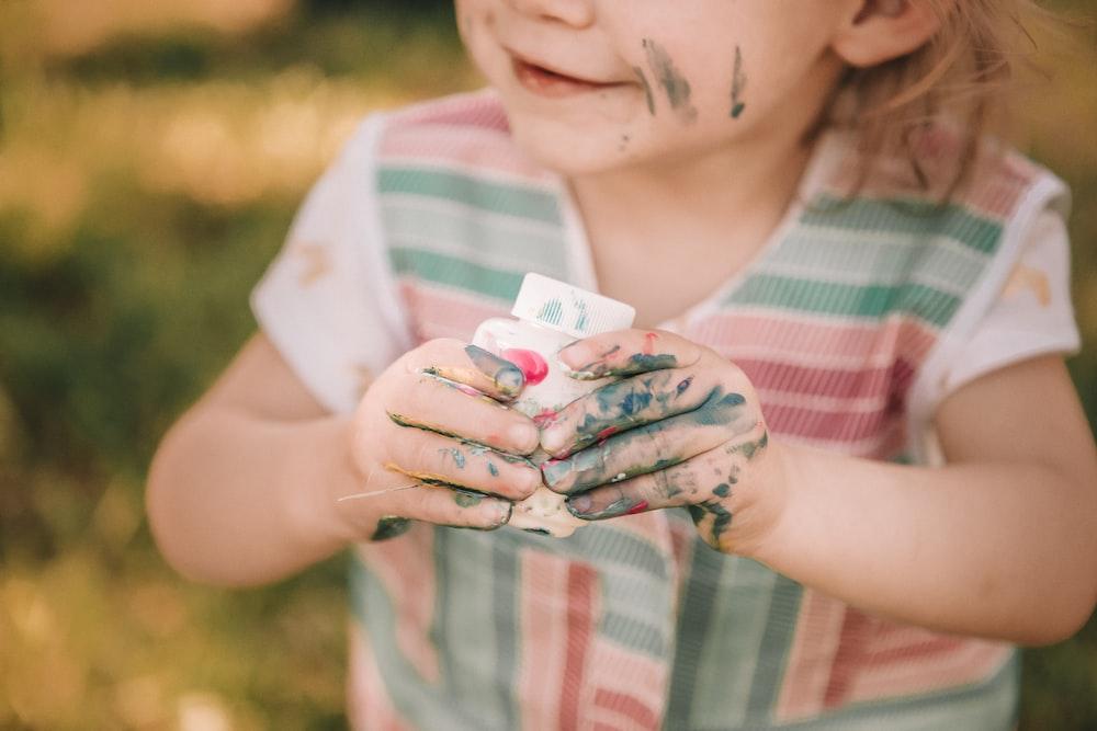 toddler holding white case