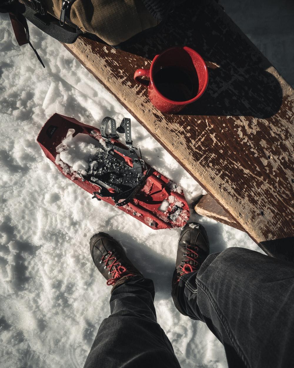 red ceramic mug on wooden bench outside snow