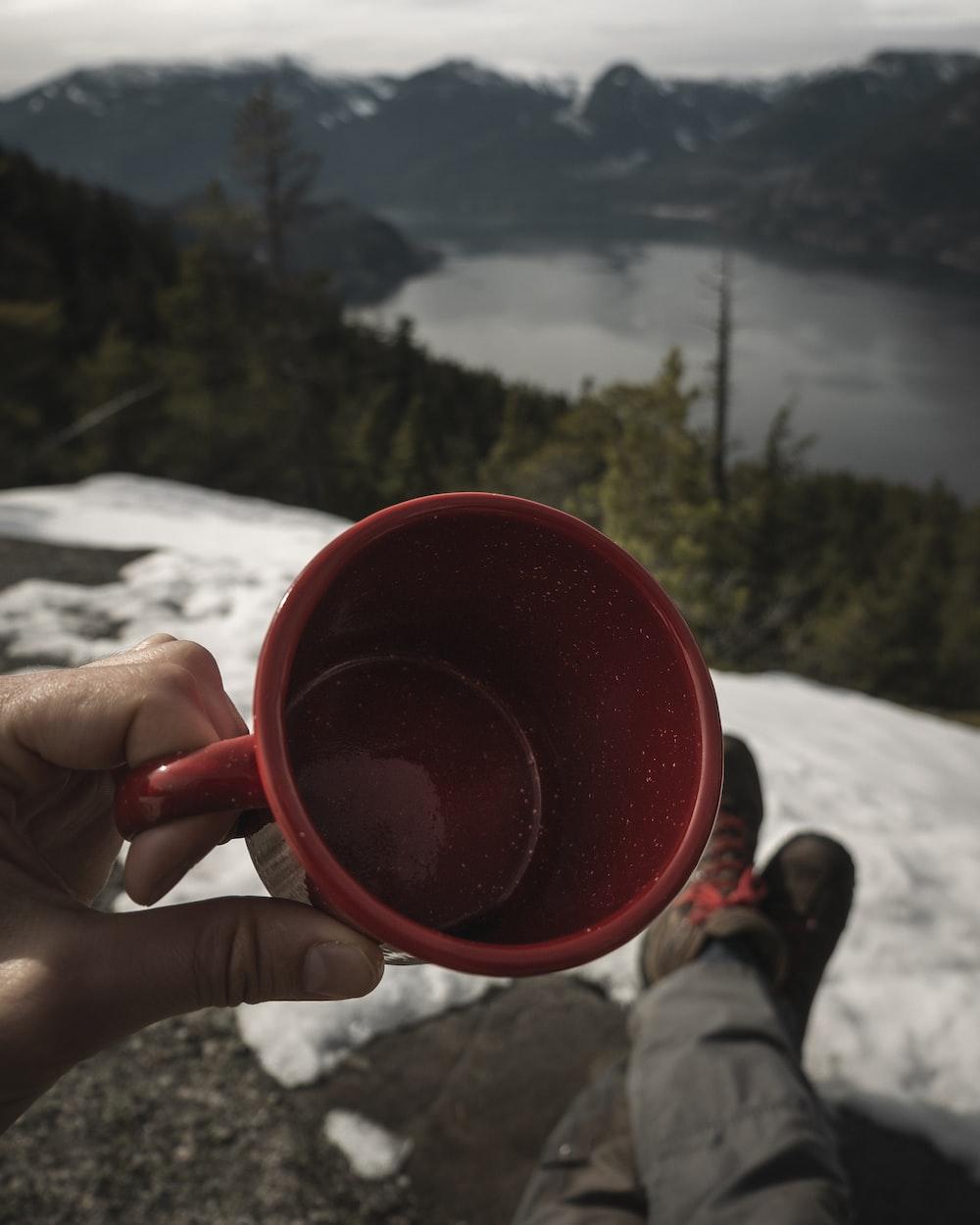 person holding red ceramic mug