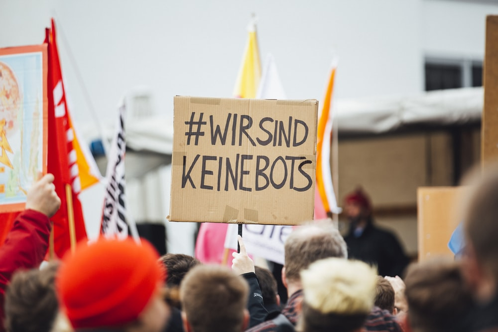 person raising wirsind keinebots signboard