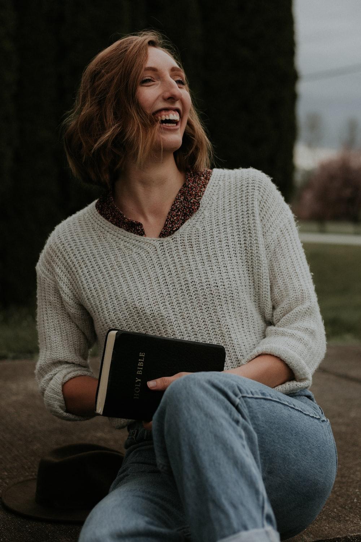 smiling woman wearing white knit sweater