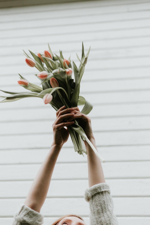 woman raising bouquet of tulips