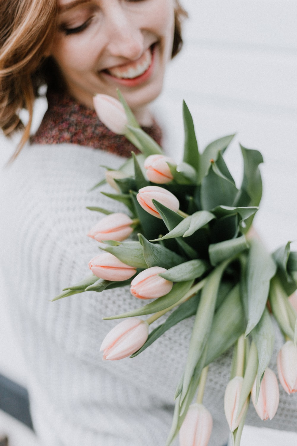 woman clutching bouquet of pink flowers and smiling