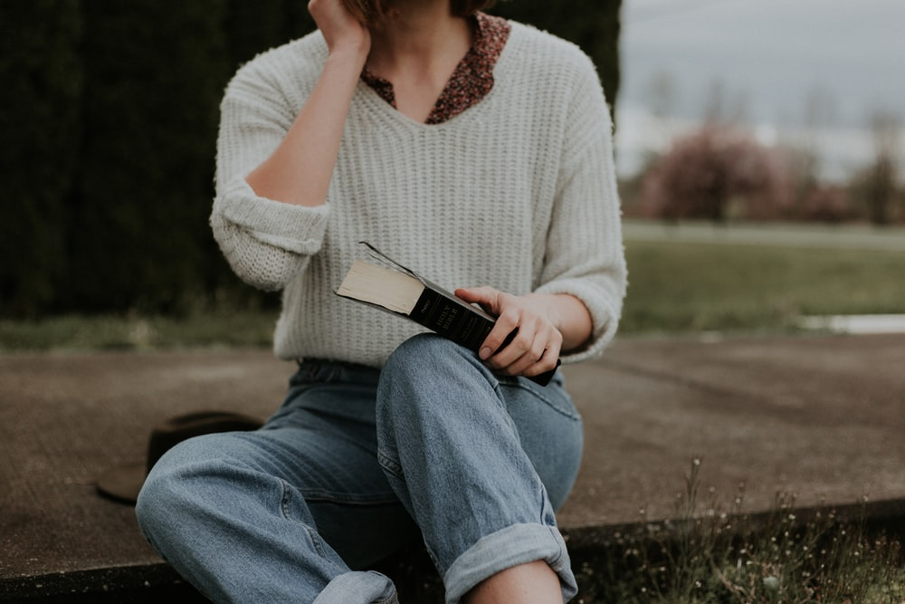 woman sitting while holding book