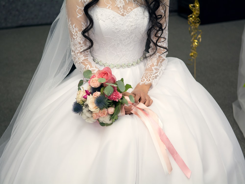 woman sitting while holding bouquet of flowers