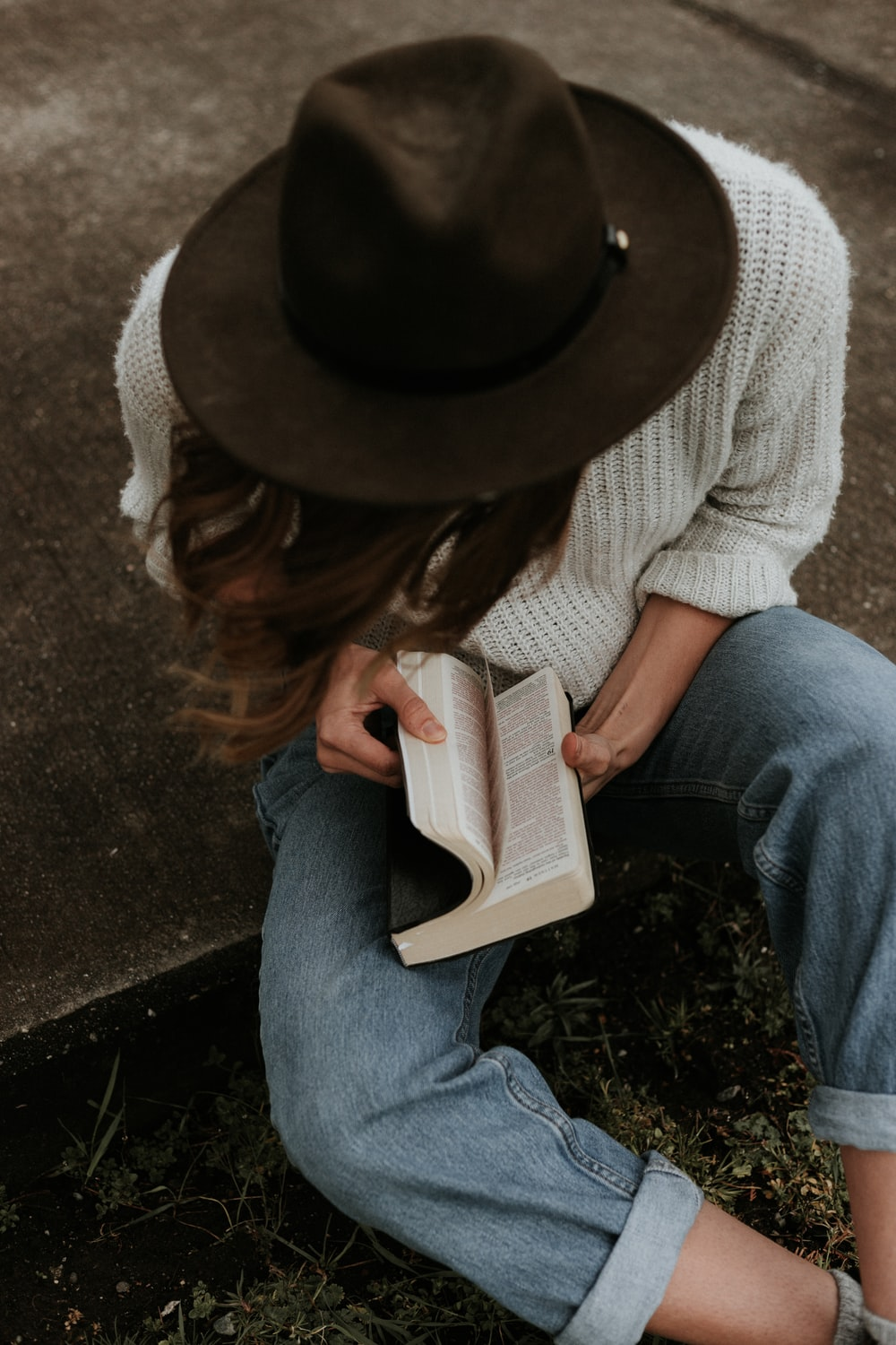 woman sitting on ground while opening book