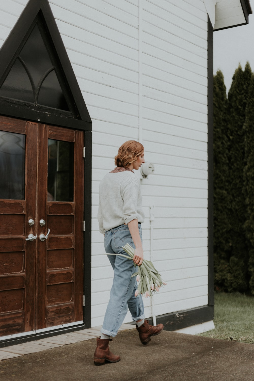 woman walking in front of closed door with flowers on hand