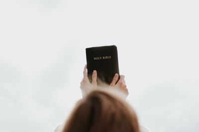 person holding holy bible diploma teams background