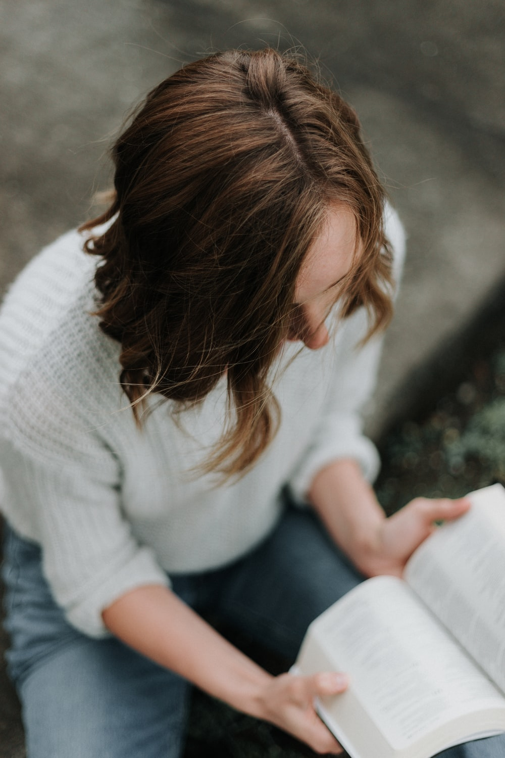woman sitting on floor while reading book