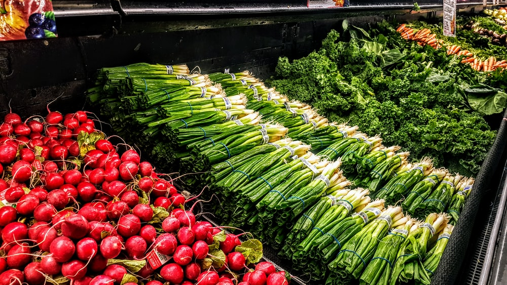pile of red radishes, scallions, and green leafy vegetables
