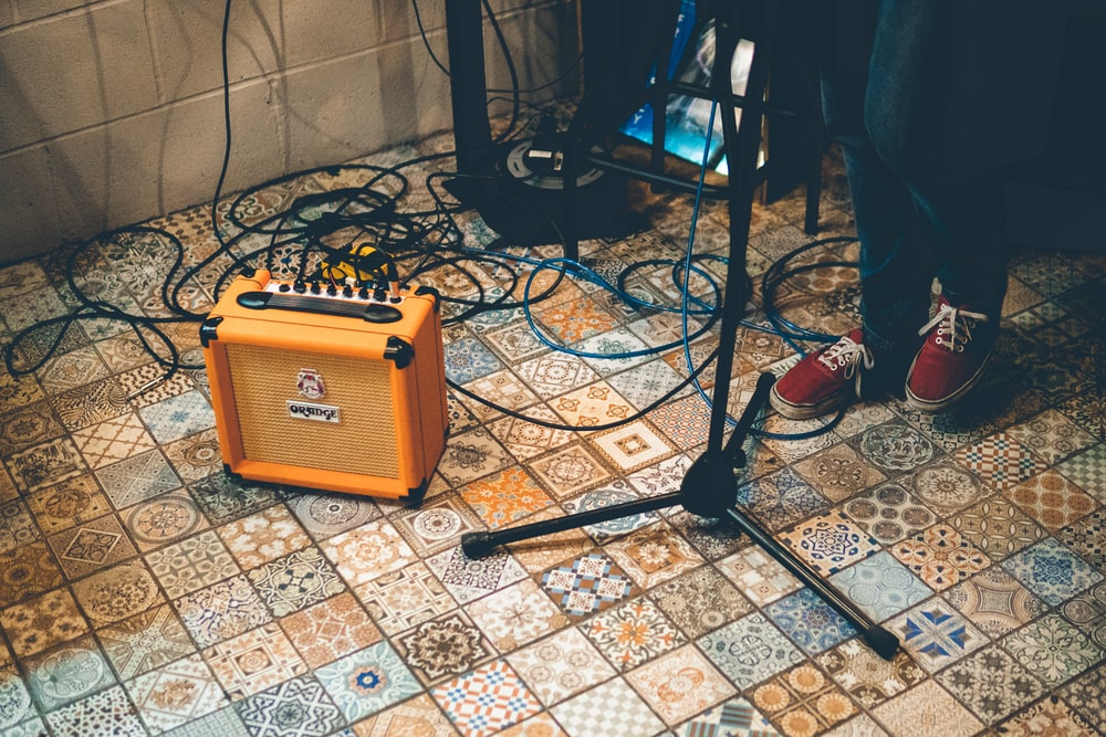 person standing near stand and orange amplifier