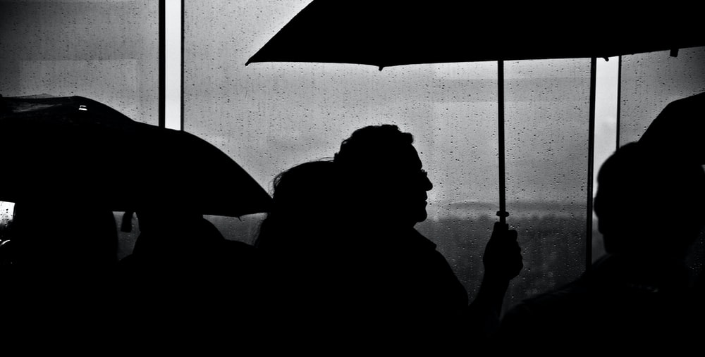 silhouette of people holding umbrella