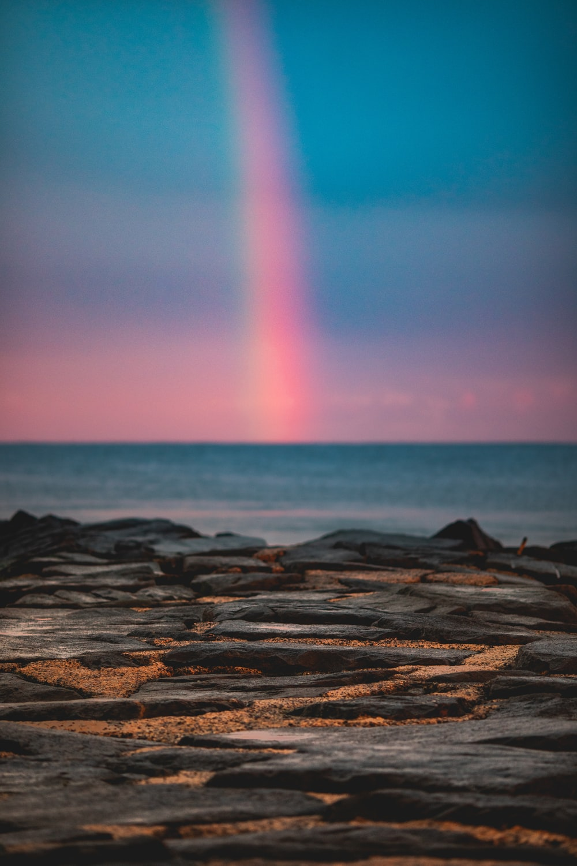 rainbow at sea during sunset