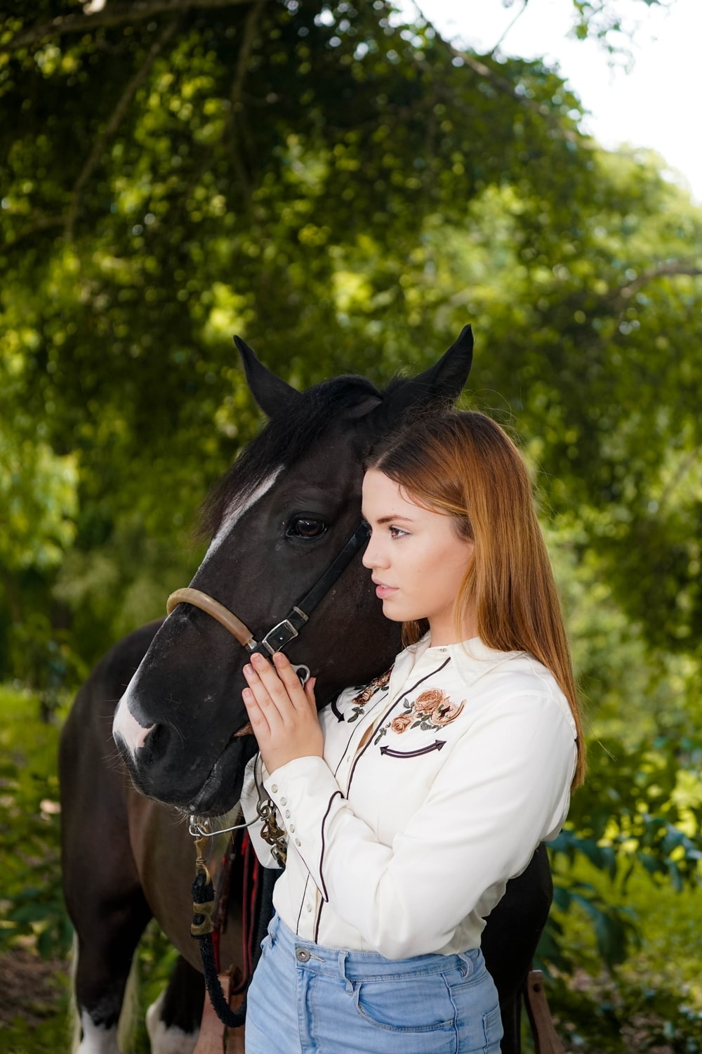 woman beside black horse during daytime