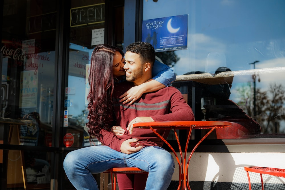 woman kissing man's cheek at daytime