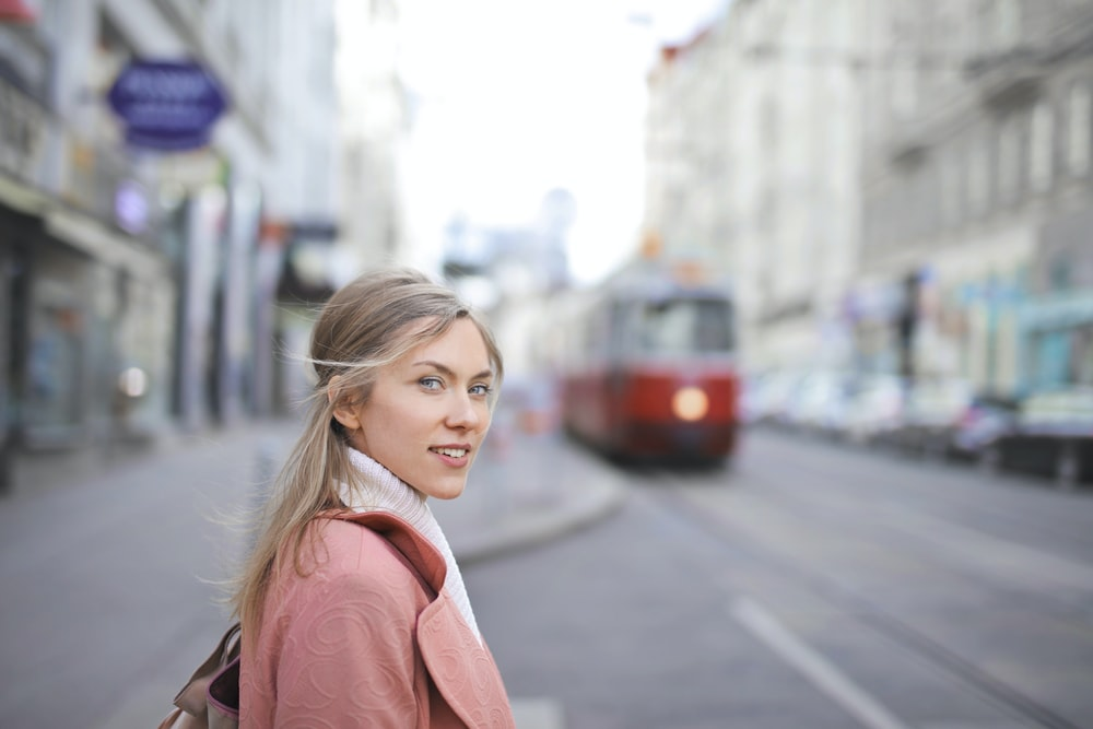 selective focus photography of woman standing near train during daytime