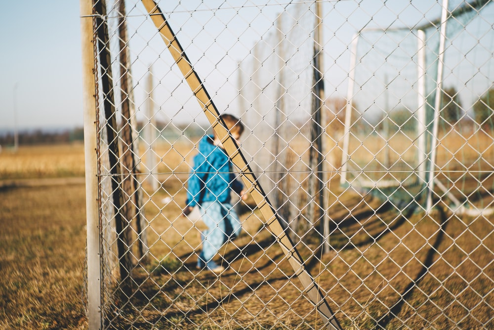 boy standing inside cyclone fences during daytime