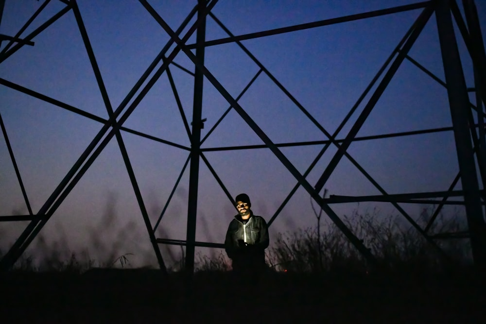 man standing under tower at night