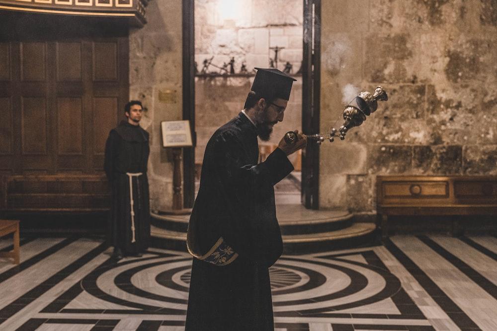man holding incense burner inside building