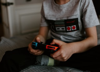 kid sitting on gray bed while playing