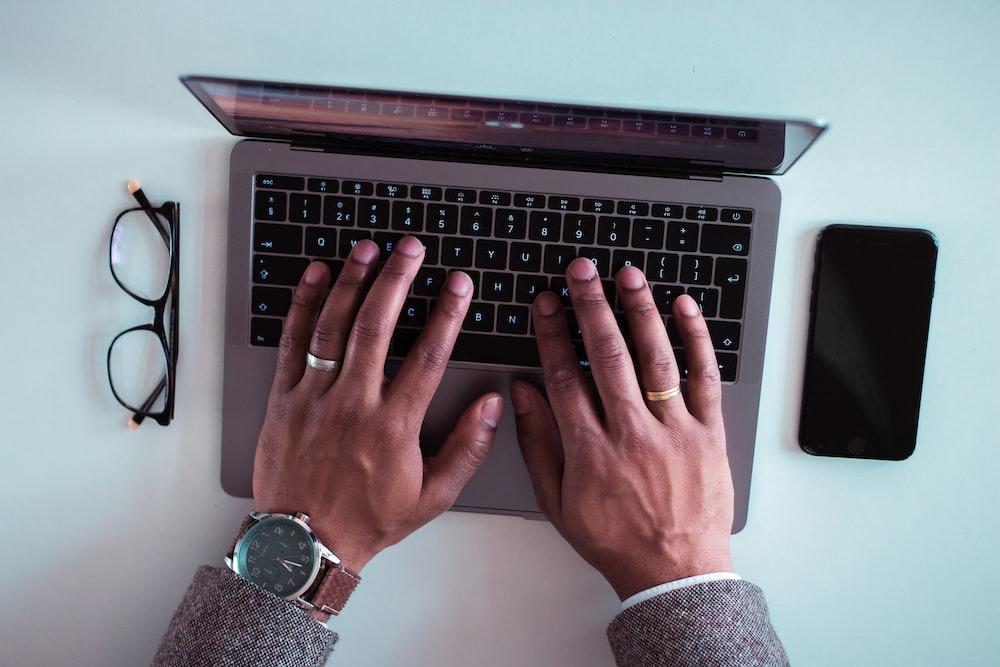 man using laptop between eyeglasses and iPhone
