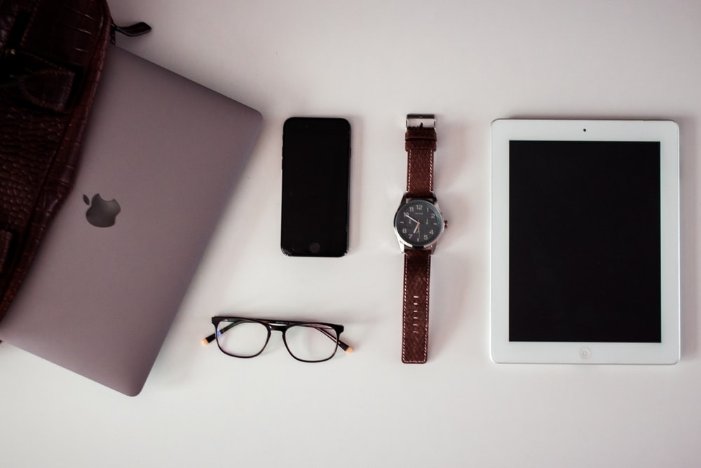 white iPad beside round silver-colored analog watch, black iPhone 5 and black framed eyeglasses on white surface