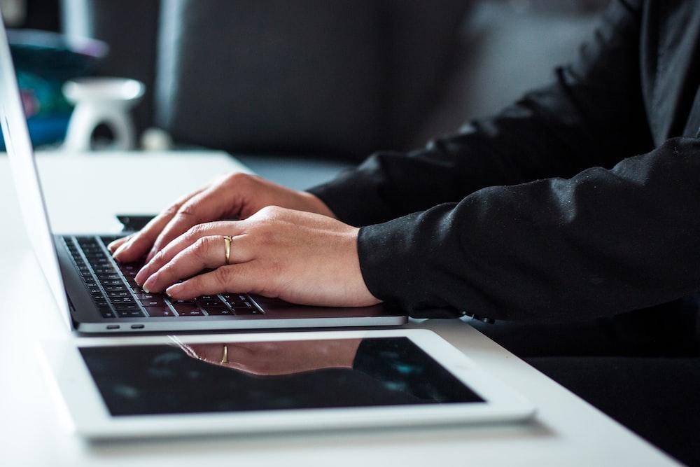 man in black dress shirt using laptop