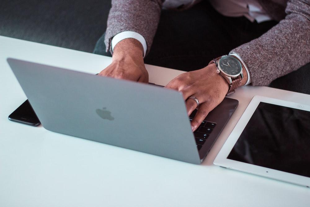 man using MacBook between iPad and iPhone