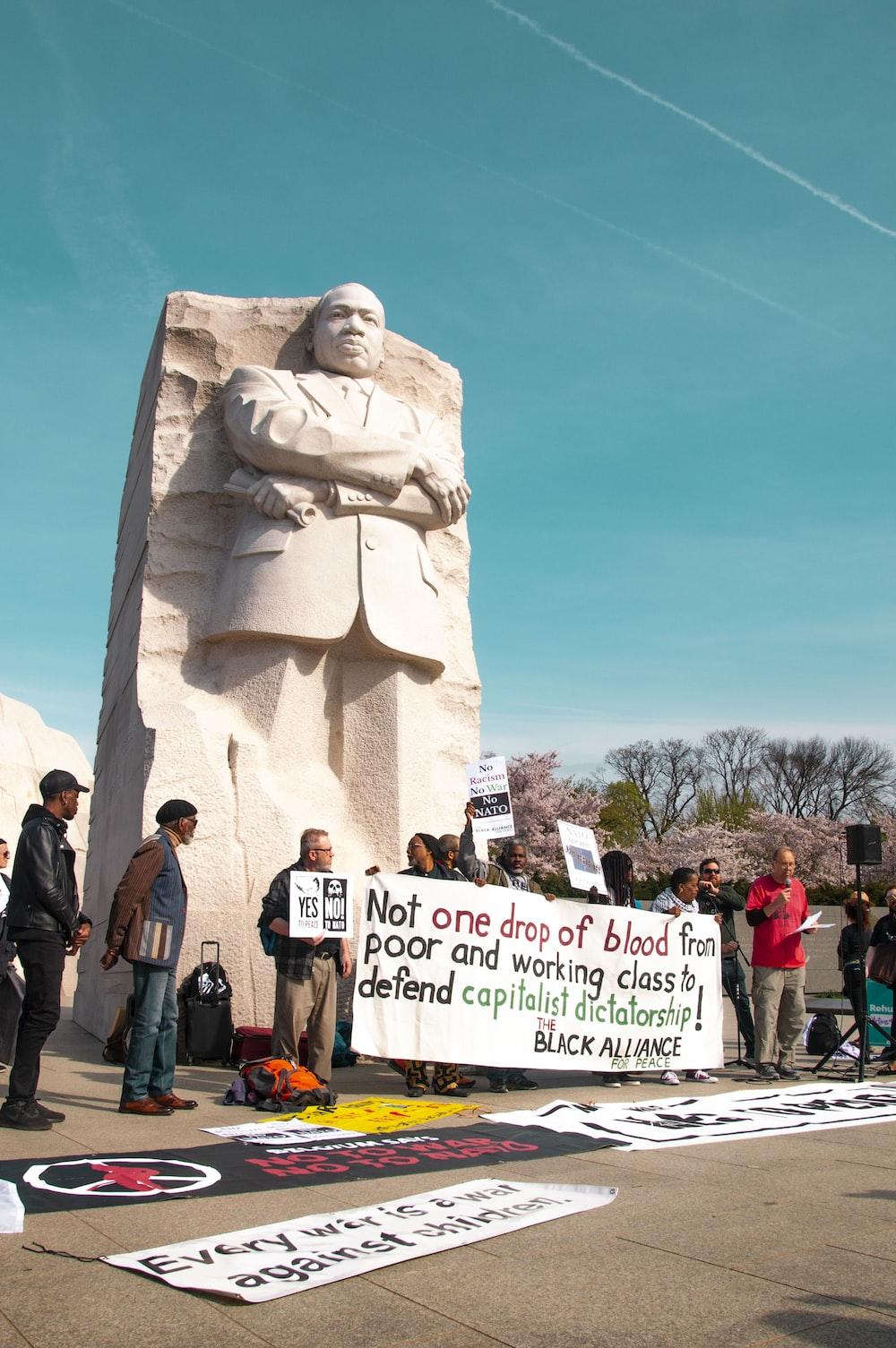 people standing beside statue
