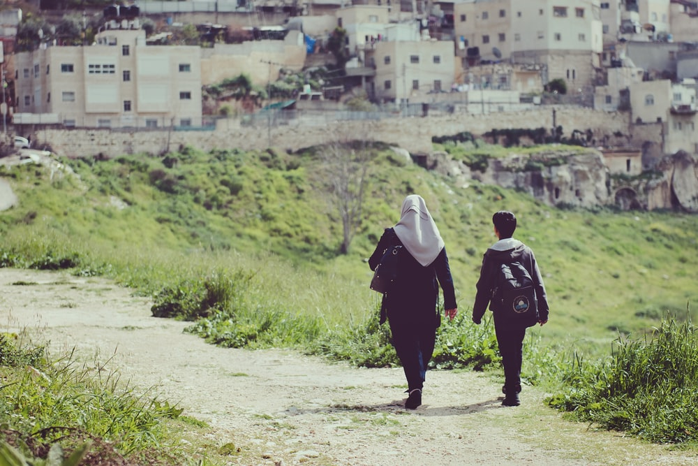 two person walking towards rural area